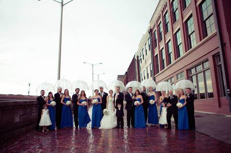 Wedding party decked out with clear umbrellas doesn't let the rain stop them from taking pictures around downtown Knoxville